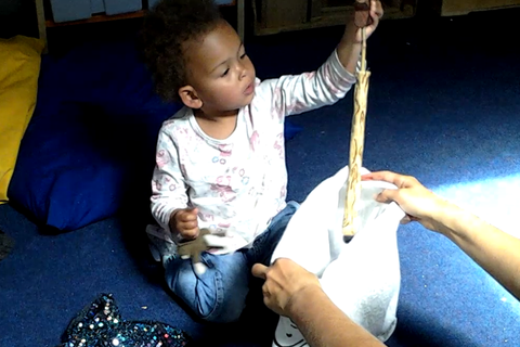 image of 2yr old pulling item out of the Tales Toolkit bag